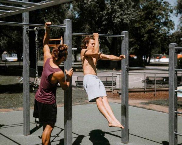 Luis und Fernando beim Training draussen im Calisthenics Park. Luis kontrolliert seinen Bruder Fernando dabei, wie er mit einem Arm an einer Stange trainiert.