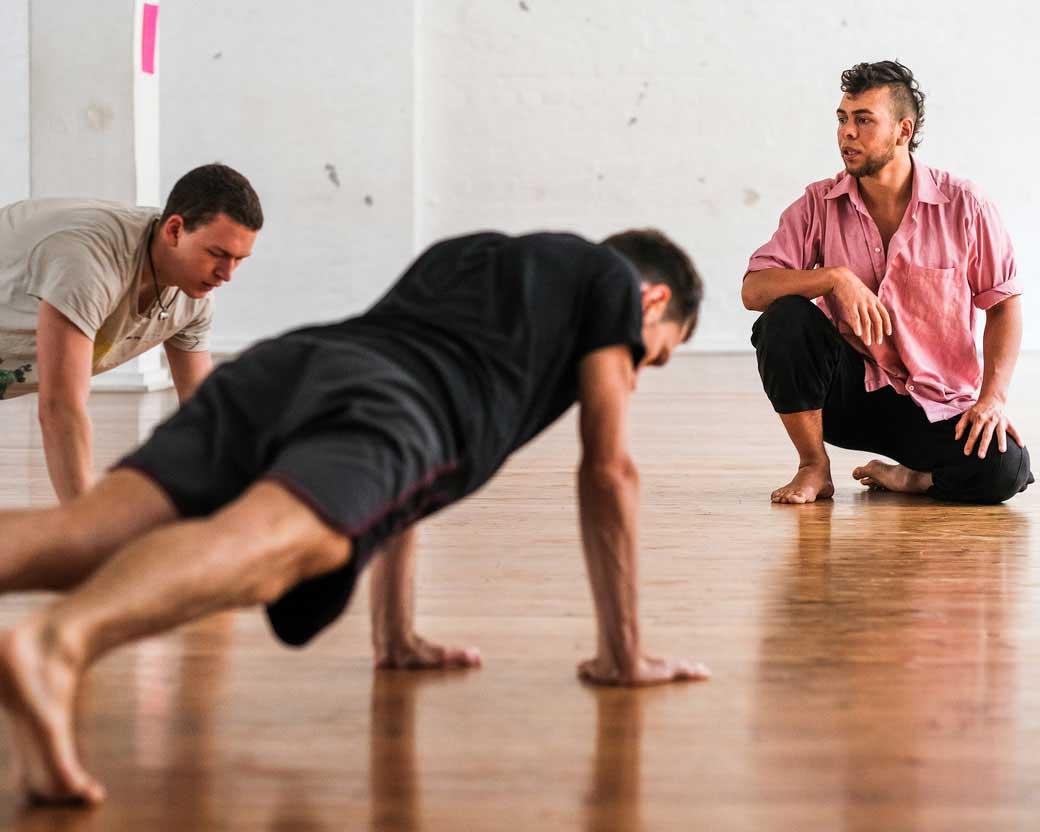 Luis Stängl bei einem Kurs. Luis kontrolliert zwei Schüler bei korrekten Liegestützen.