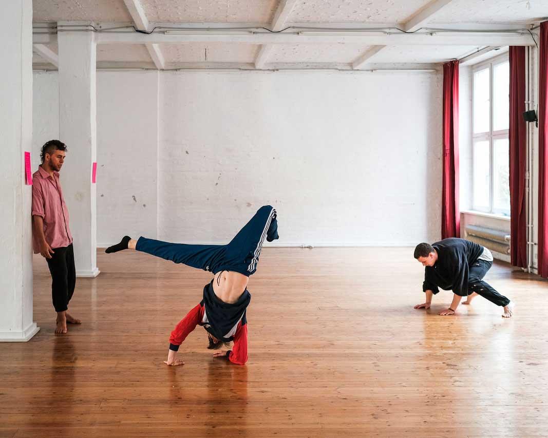 Luis Stängl beim Handstand Workshop. Luis beobachtet im Tanzstudio zwei Schüler bei Handstand Übungen