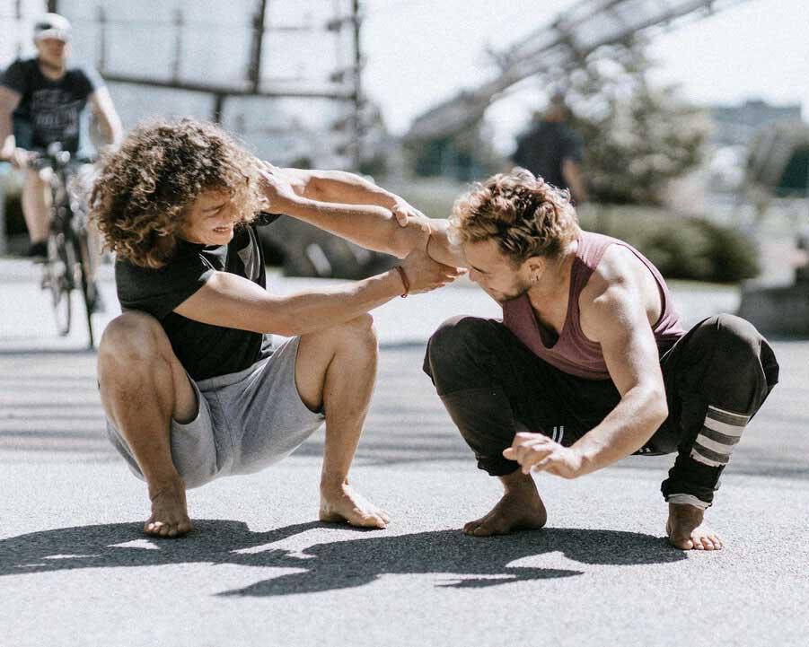 Fernando und Luis Stängl beim gemeinsamen Outdoor Training. Die beiden Brüder sind in der Hocke und ziehen gegenseitig an sich als Balance Übung